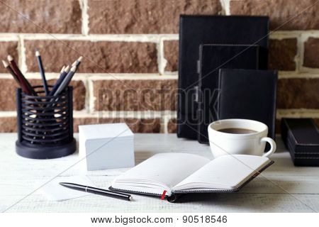 Stylish workplace at home or studio, on brown bricks background