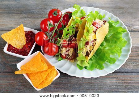 Tasty taco with nachos chips and tomato dip on plate on table close up