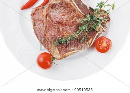 savory : roasted beef spare rib on white dish with cutlery thyme pepper and tomato isolated over white background