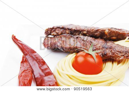 grilled beef fillet with pasta and tomatoes on white plate isolated over white background