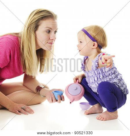 An adorable 2-year-old looking at her mommy as she points in another direction.  On a white background.