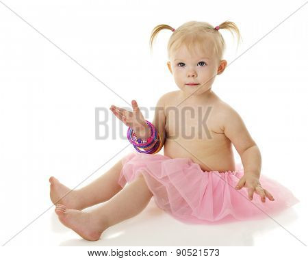 An adorable 2-year=old looking up as she wears an armful of colorful bangles.  On a white background.