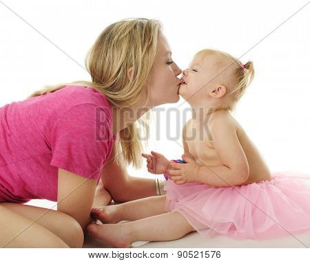 A mother and her adorable, laughing 2-year-old kissing.  On a white background.