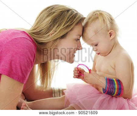 An adoring mother watching closely as her 2-year-old plays with colorful bangles.  On a white background.
