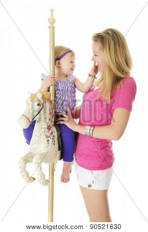 An adorable 2 year old and her mom having fun with the carousel horse.  On a white background.