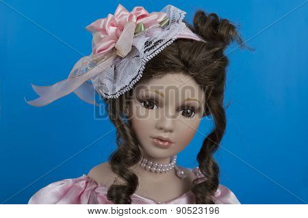 Pretty Doll Face Wearing Hat Over Blue Background