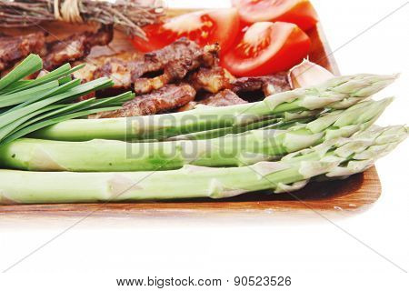 hot lunch of fresh beef meat roasted ribs with asparagus and tomatoes isolated over white background