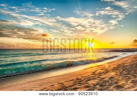 Beautiful sunset over the sea with a view at stony shore on the white beach on a Caribbean island of Barbados