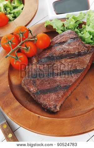 dinner of fresh rich juicy grilled beef meat steak fillet with marks on wooden plate over white table served with vegetable salad and cutlery, new york styled cuisine