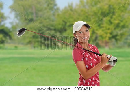 Beautiful young woman playing golf on the course