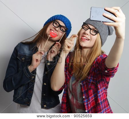 two young funny women taking selfie with mobile phone