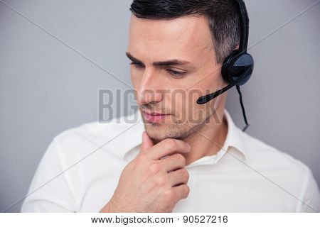 Portrait of a pensive male operator over gray background