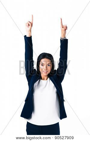 Happy businesswoman pointing fingers up over white background. Looking at camera