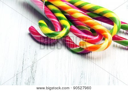 Colorful candy canes in glass on wooden background
