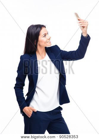 Smiling businesswoman making selfie photo on smartphone over white background