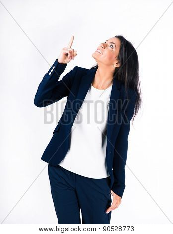 Smiling businesswoman pointing finger up over white background. Looking up
