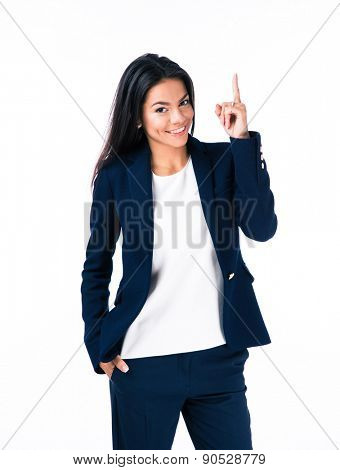 Portrait of a happy businesswoman pointing finger up over white background and looking at camera