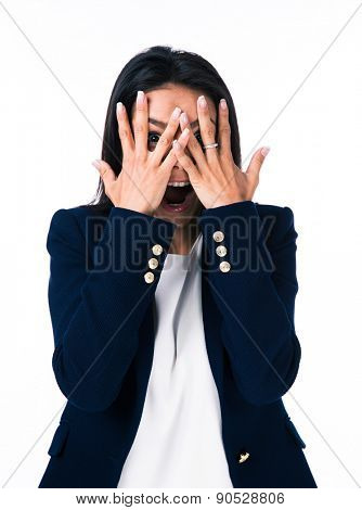 Businesswoman covering her eyes with hands and looking at camera through fingers. Isolated on a white background