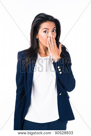 Attractive businesswoman covering her mouth with hand over white background and looking at camera