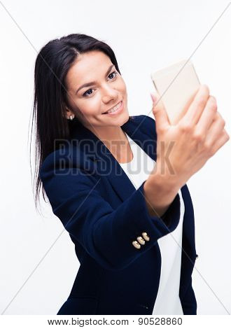 Happy businesswoman making selfie photo on smartphone over white background