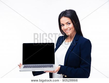 Cheerful businesswoman presenting laptop over white background. Looking at camera