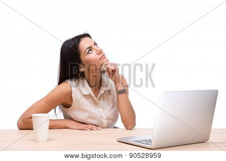 Thoughtful businesswoman sitting at the table with laptop and looking up over white background