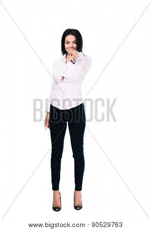 Full length portrait of a beautiful businesswoman pointing finger at camera. Isolated on a white background