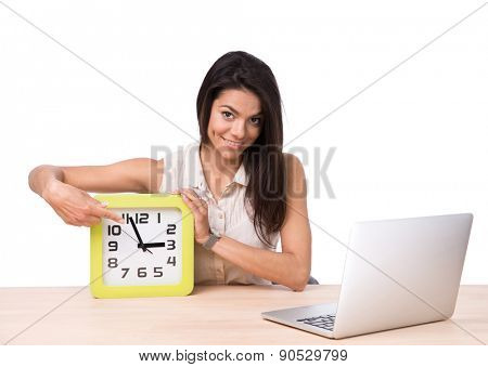 Businesswoman sitting at the table with laptop and pointing finger on the clock over white background. Looking at camera