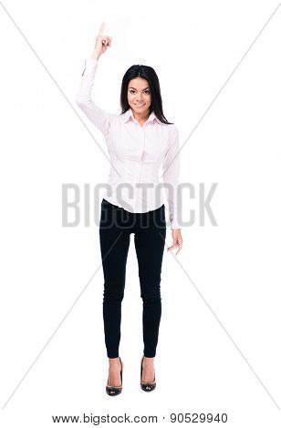 Full length portrait of a smiling businesswoman pointing finger up. Isolated on a white background. Looking at camera