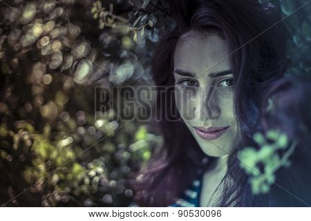 Outdoor, melancholy young girl in a forest with sad gesture