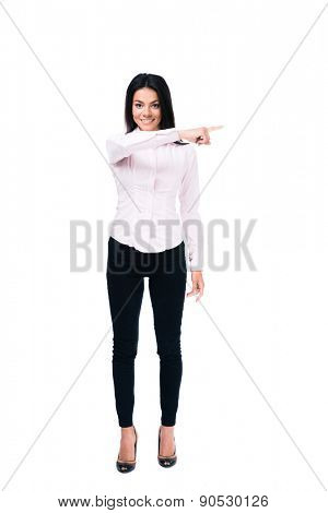 Full length portrait of a smiling businesswoman pointing finger away isolated on a white background. Looking at camera