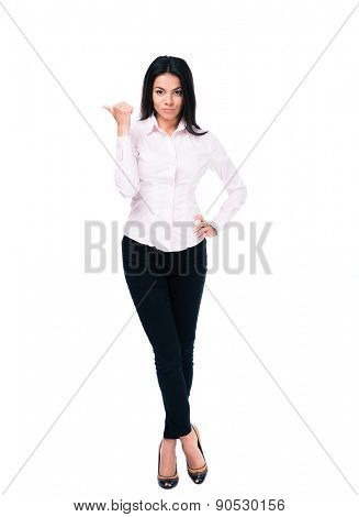 Full length portrait of a serious businesswoman pointing finger away isolated on a white background. Looking at camera