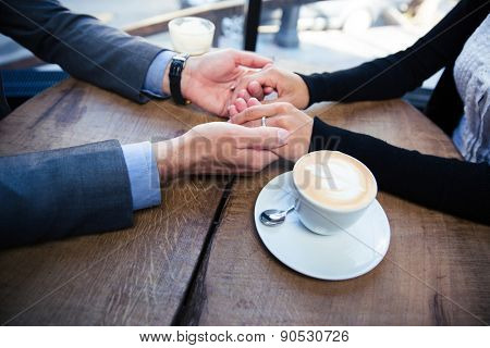 Closeup image of a man holding his girlfriend's hand at the restaurant