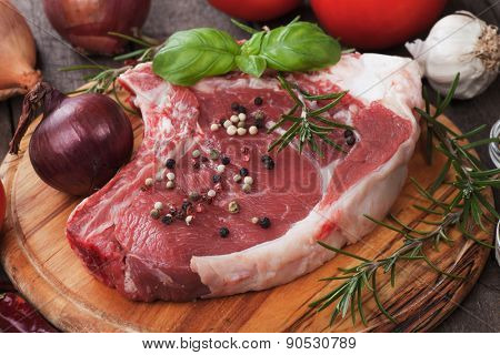 Raw ribeye beef steak on wooden board with rosemary and peppercorn