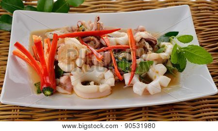 Hot And Spicy Stir Fried Squid With Basil Leaf On Plate With Rattan Background