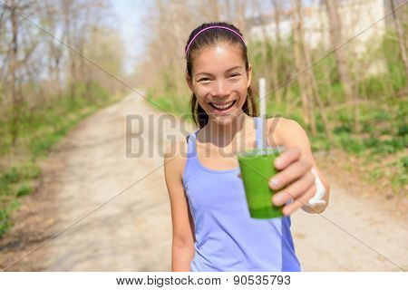 Green vegetable smoothie - healthy lifestyle and eating concept. Close up of green vegetable detox smoothie with spinach. Woman hand holding vegetable smoothies outdoors in forest.