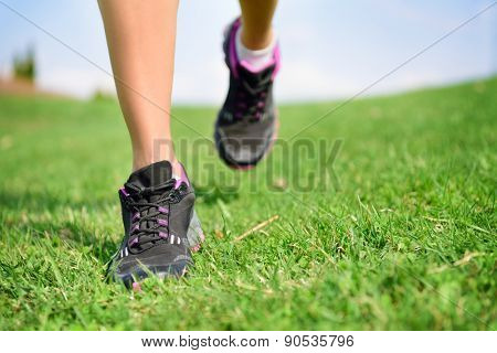 Runner athlete feet running on grass. Fitness woman jog workout and wellness concept. Close up of female running shoes and legs.