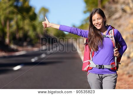 Travel hitchhiker woman backpacking hitchhiking thumbing happy walking on road side during holiday travel. Beautiful outdoors woman model. Mixed race Asian Caucasian