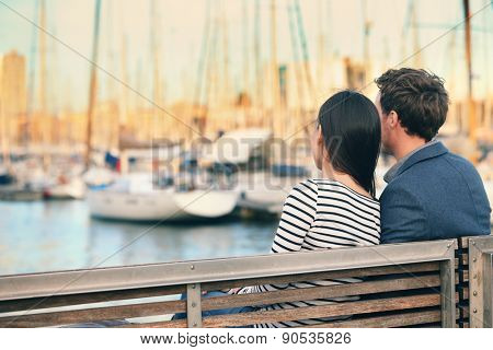 Lovers couple Romantic dating sitting on bench on date in old harbour, Port Vell, Barcelona, Catalonia, Spain. Happy woman and man embracing enjoying life and romance outside