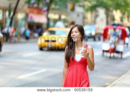 Casual young urban woman drinking coffee happy smiling in New York City, Manhattan. Girl drinking hot drink from disposable cup walking in street wearing red dress with yellow taxi cabs in background.