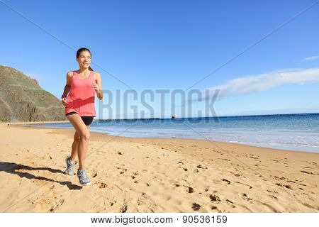 Jogging sports athlete runner woman running on beach sweating. Fit exercising female fitness model working out training for marathon run. Biracial Asian Caucasian sports girl.