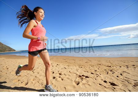 Sports athlete runner running woman on beach sweating and jogging. Fit exercising female fitness model in workout training outdoors. Biracial Asian Caucasian sports girl.