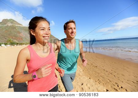 Running couple jogging on beach exercising and jogging training. Runners working out on summer beach.