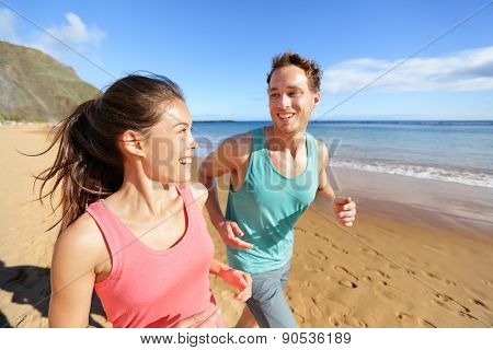 Young couple talking running on beach jogging. Athletes smiling happy working out training workout. Exercising Asian woman and Caucasian fitness man.