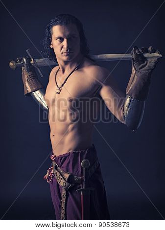 Half-naked Man With A Sword In Medieval Clothes On A Dark Background