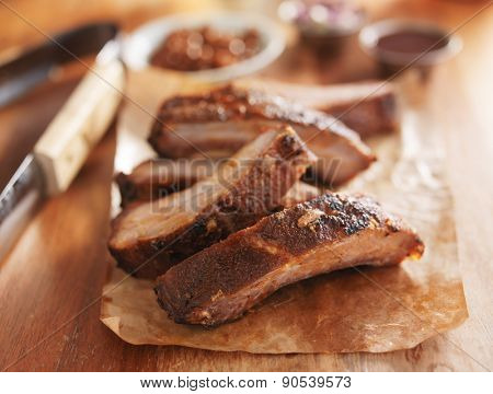 barbecue pork spare ribs on cutting board with tongs