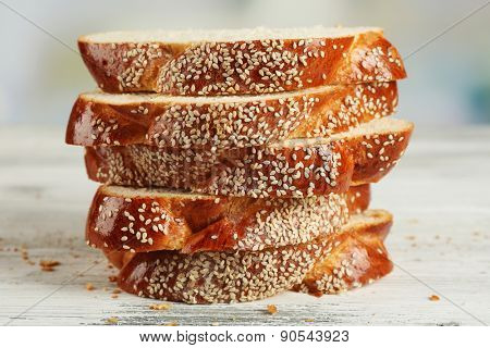 Sliced fresh bun with sesame on table on bright background