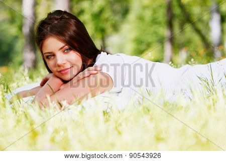 Young beautiful woman waking up on grass outdoors