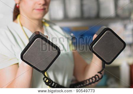 Female Nurse In Icu In Green Uniform With Defibrillator