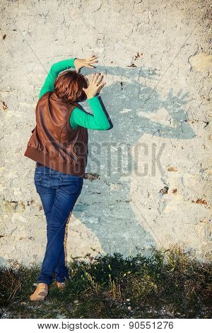Young Woman Making Shadows Shapes With Her Hands In Front Of The Old Wall